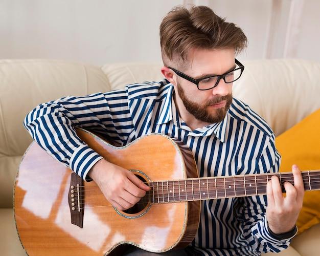 Человек играет на гитаре у себя дома на диване