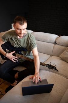 家でギターを弾く男