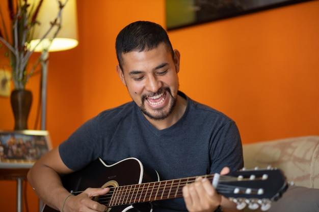 自宅でギターを弾く男