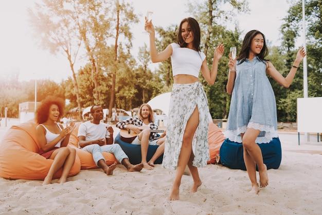 Man playing guitar on beach young women dancing.
