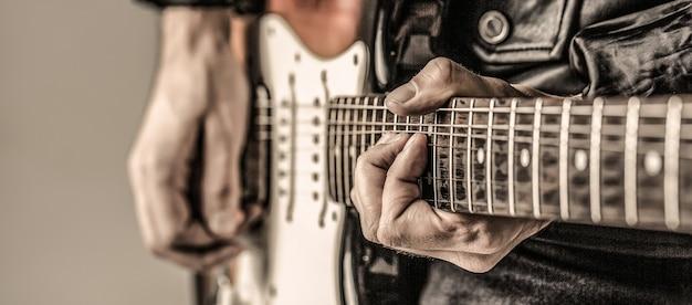 Человек играет на гитаре. закройте вверх по руке, играя на гитаре. музыкант играет на гитаре, играет живая музыка.
