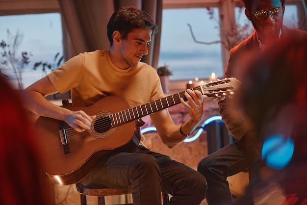 Человек играет на гитаре для своих друзей