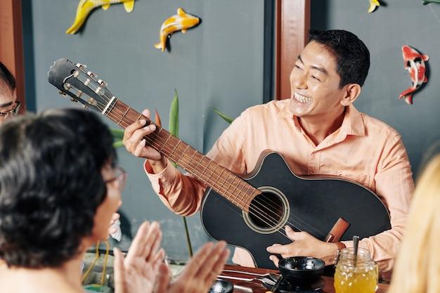 Человек играет на гитаре для друзей и родственников