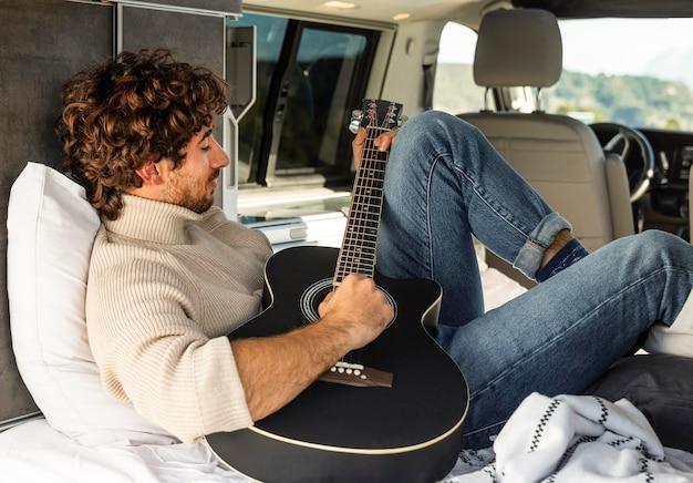 Uomo che suona la chitarra dall'auto durante un viaggio su strada