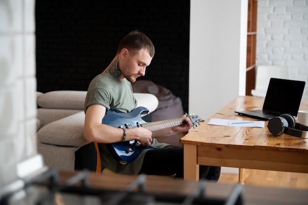 Uomo che suona la chitarra a casa