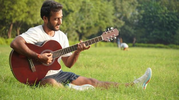 Человек играет на гитаре в парке