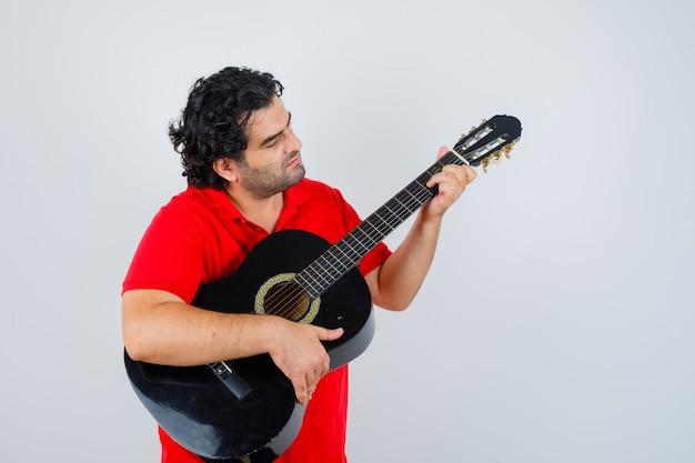 赤いtシャツでギターを弾き、集中して見える男