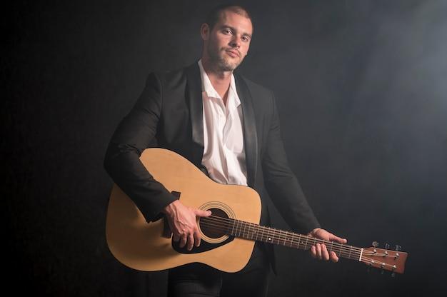 スタジオでギターを弾く男