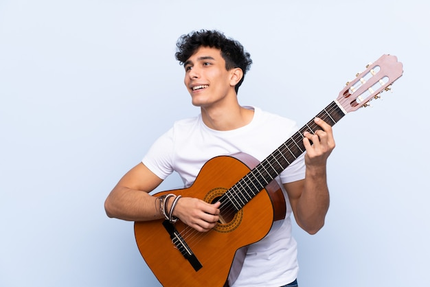 Man playing guitar over isolated wall