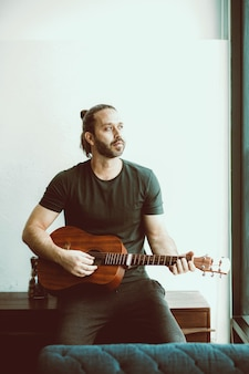 Man playing guitar looking away missing someone single lonely at home vintage color tone vertical shot.