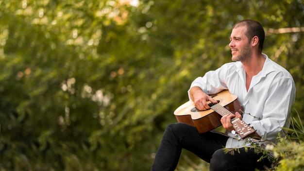 Uomo che suona la chitarra nello spazio della copia della natura