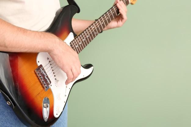 グリーンでギターを弾く男