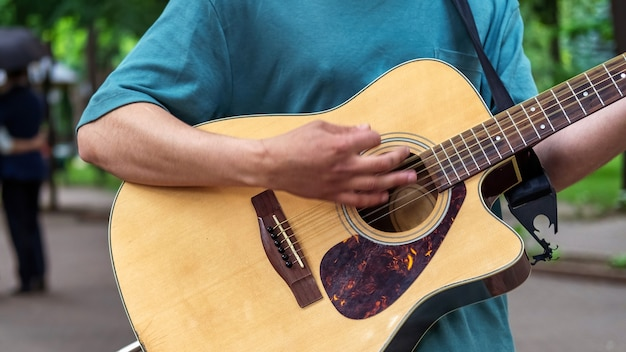 공원에서 야외에서 기타를 치는 남자 프리미엄 사진