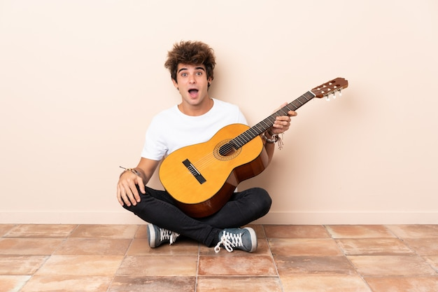 Man playing the guitar and sitting on the floor