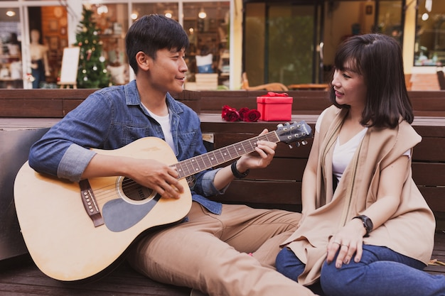 Man playing a guitar while looking at his girlfriend with a gift and a flower