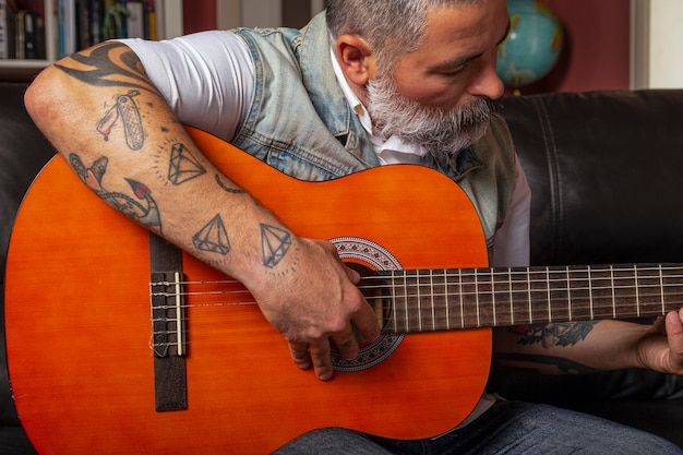 オンラインレッスンを受けながらギターを弾く男。オンライン学習の概念