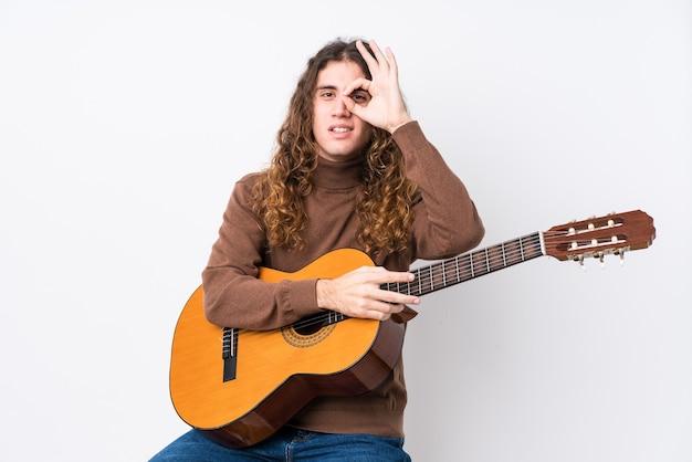 Человек играет на гитаре с хорошо жестом на глазах