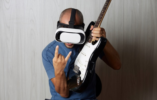 Man playing guitar with virtual reality eyeglasses