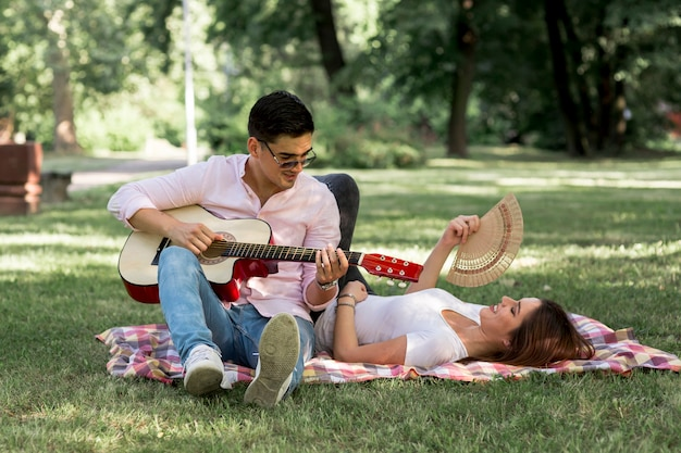 Man playing the guitar to a woman