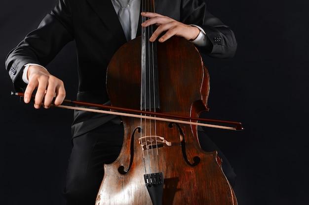 Человек играет на виолончели в темноте