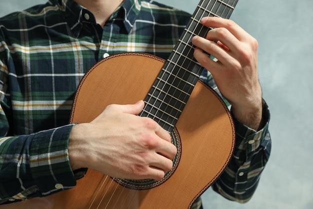 Человек играет на классической гитаре