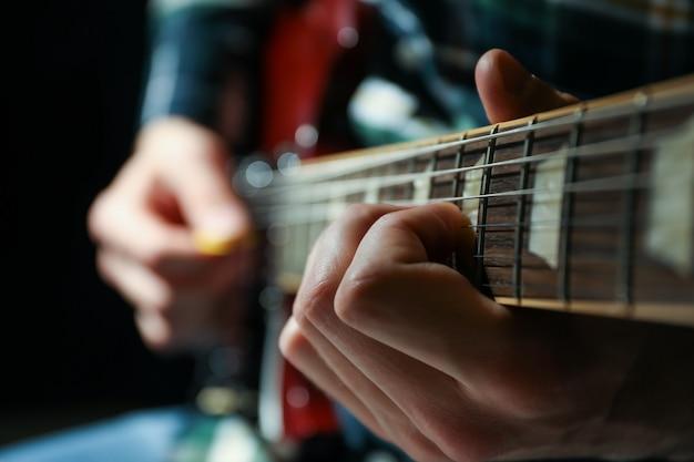 暗い背景、クローズアップに対してエレキギターで遊ぶ男