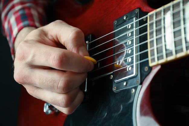 クローズアップのエレクトリックギターで遊ぶ男