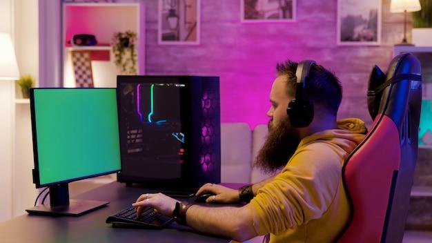 네온 불빛이 있는 방에서 강력한 게임용 pc를 가지고 노는 남자. 녹색 화면이 있는 컴퓨터.