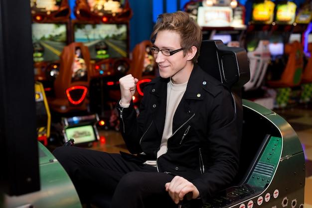 Человек играет на игровых автоматах, аттракционы в торговом центре