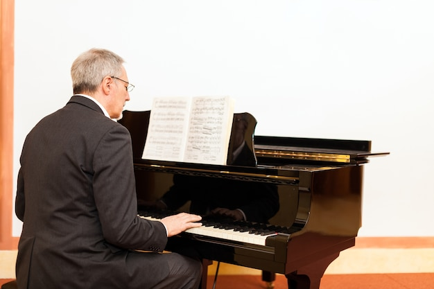 Man playing a piano in a concert hall