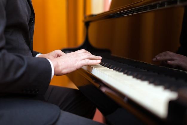 Man playing a piano. no face shown