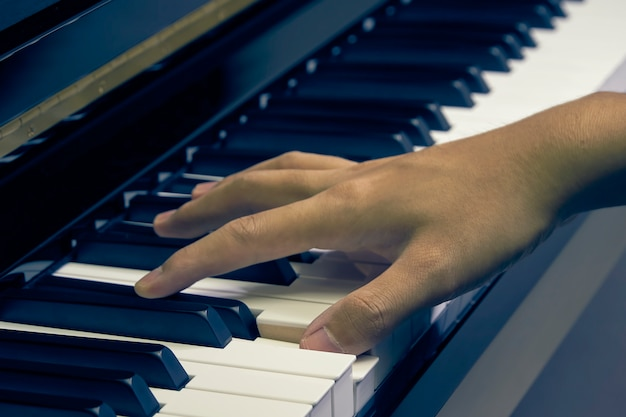 Man playing piano in the studio with blurred hand