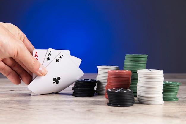 Человек играет в покер и смотрит на тузов на столе