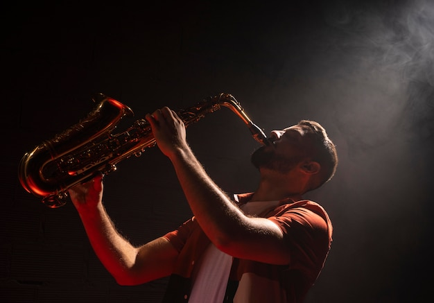Man playing the saxophone in spotlight