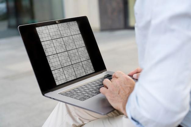 ノートパソコンで数独をしている男