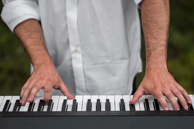 Man playing synthesizer keyboards outdoors close-up