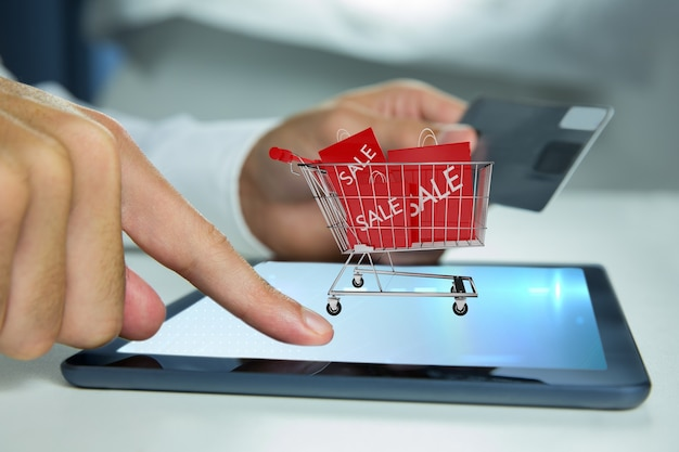 Man playing a tablet with a shopping cart