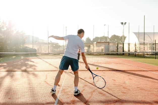 日光の下で朝にテニスをしている人