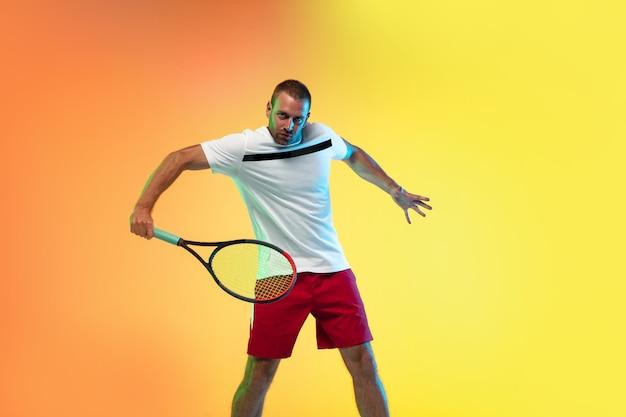 ネオンの光の中でスタジオの背景に分離されたテニスをしている男