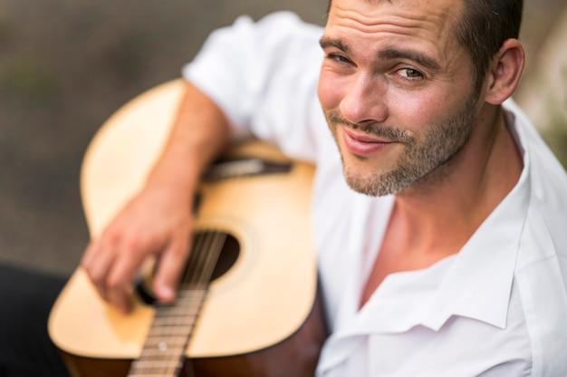 自然の中でぼやけたギターを弾く男