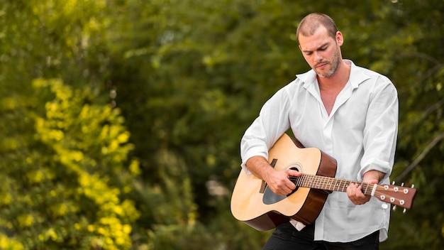 自然の中でギターを弾く男