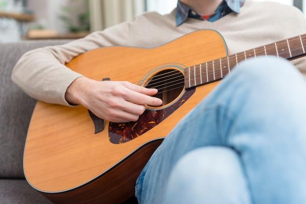 室内でギターを弾く男