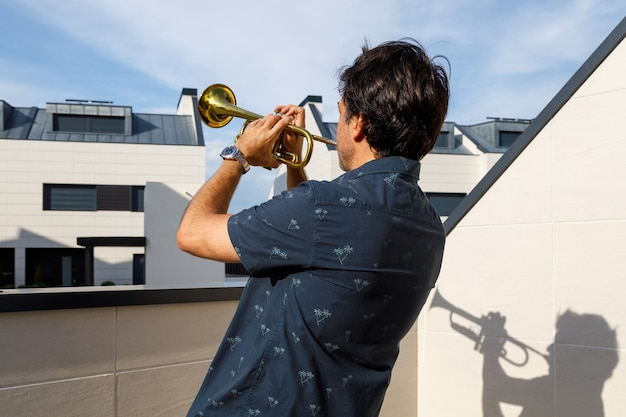 Man playing trumpet on thr terrace in summer. side view. covid - 19
