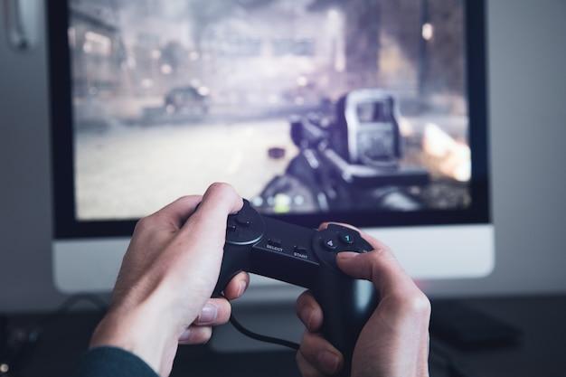 비디오 게임하는 남자. 콘솔 컨트롤러를 들고 손