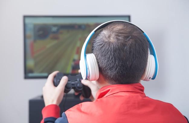 Человек играет в видеоигры дома.