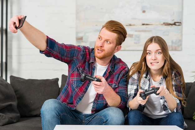 Man playing video game with her girlfriend taking selfie on smartphone