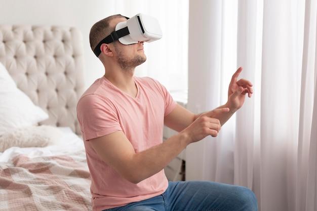 バーチャルリアリティゴーグルを着用しながらビデオゲームをプレイする男