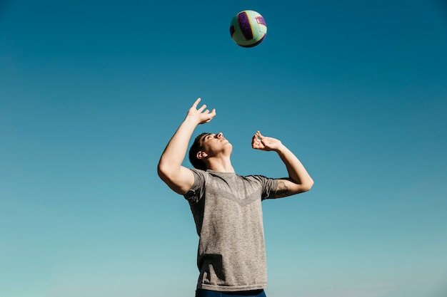 ビーチでバレーボールをする男