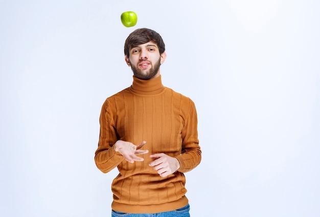Человек играет с зеленым яблоком и подбрасывает его.