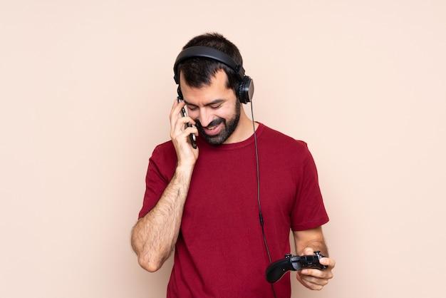 Человек играет с контроллером видеоигры над изолированной стеной, ведя разговор с мобильным телефоном